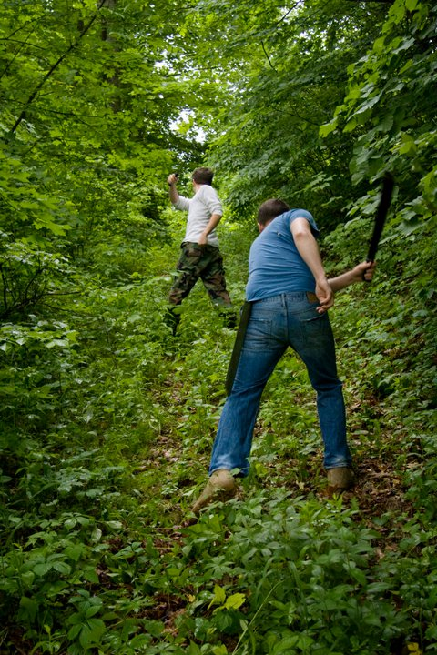 Curry and Chet prove their manliness by chopping down the forrest with machetes.